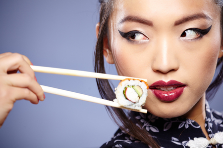 Photo pour Sushi woman holding sushi with chopsticks looking at the camera smiling. - image libre de droit