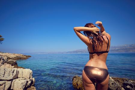 Foto de Fashion style full length portrait of young beautiful sexy tanned girl in white bikini at rocks near blue green clear ocean sea water. - Imagen libre de derechos