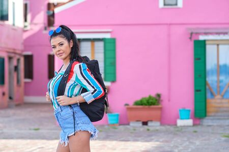 A girl with a backpack visits a colorful Italian town