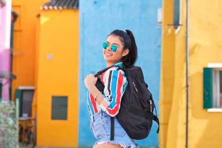 girl with a backpack visits a colorful Italian town