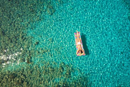 Photo pour A beautiful young girl lies on a mattress in the open sea or in the pool, a pink bikini, blue clear water, a top view. - image libre de droit