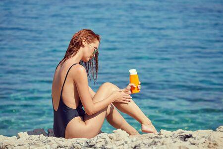 Photo pour sexy young woman on the beach applying sun cream - image libre de droit