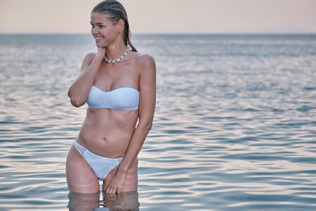 Photo pour Portrait of young woman in white bikini on beach .Beautiful caucasian girl in swimwear with copy space. Summer vacation and tanning concept. - image libre de droit