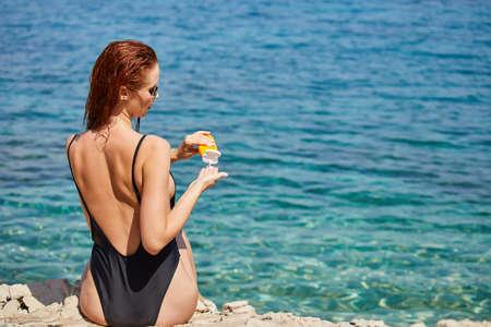 Photo pour Woman applying sunscreen creme on tanned shoulder over the sea - image libre de droit