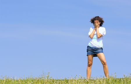 Crying teen girl against a blue sky with space for text on left
