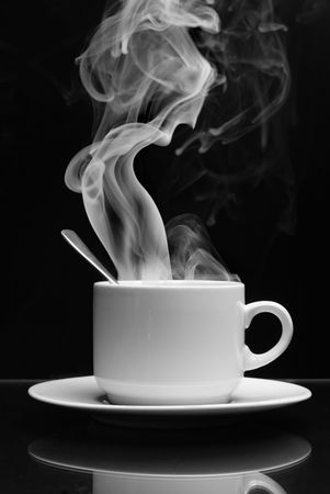 Photo pour Cup of hot drink with steam over black background - image libre de droit