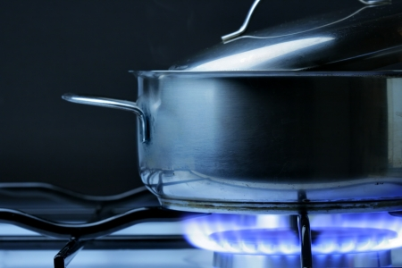 Crock on the gas stove over black background