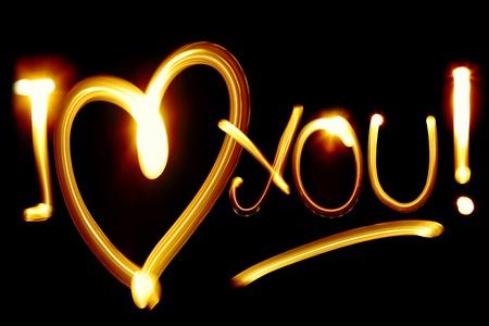 Photo pour I LOVE YOU phrase created by light over black background - image libre de droit