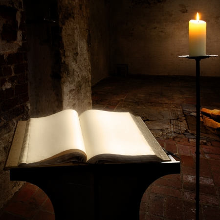 Open book with blank pages and candle