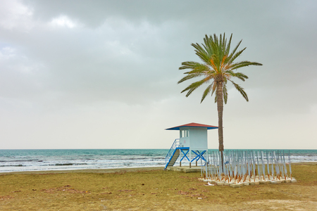 Photo pour Mackenzie beach with palm tree and life guard tower, Larnaca, Cyprus - image libre de droit