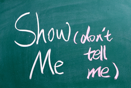 The phrase Show Me, Don't Tell Me written by hand on chalkboard. Often used in business but more so as a guide for novel and book writers
