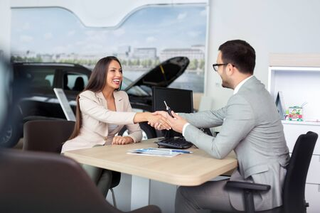 Photo pour Car salesman giving the key of the new car to the young attractive girl - image libre de droit