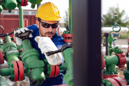 Photo for Oil worker turning valve on oil rig - Royalty Free Image
