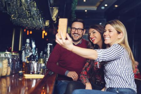 Photo pour Three friends taking selfie in a bar. - image libre de droit