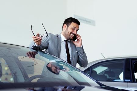 Photo pour Businessman having a phone call at the car showroom - image libre de droit