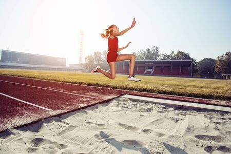 Photo for Female athlete jumping at training at stadium. - Royalty Free Image
