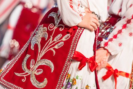 Photo pour Close up s of young Romanian dancers perform a folk dance in traditional folkloric costume. Folklore of Romania - image libre de droit