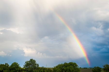 Photo for Rainbow over trees and agricultural fields with cloudy sky in background - Royalty Free Image
