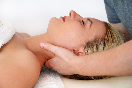 Beautiful woman during and enjoying, receiving a wellness neck massage in spa center, she is very relaxed. Woman receiving neck massage in medical office. Stretching osteopathy procedure in the neck.