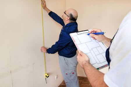 Photo pour Engineer, contractor and project manager with his colleague, construction worker, handyman and builder is measuring wall of room for renovation using measure tape and checking in apartment blueprint. - image libre de droit