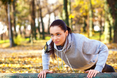 Photo pour Attractive sporty woman with headphones doing push ups outdoors in the park. - image libre de droit