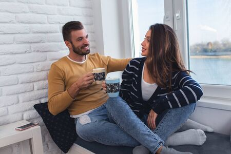 Photo pour Loving couple sitting together by the window in the apartment and drinking coffee in the morning. - image libre de droit