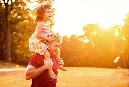 Photo pour Happy father playing and carrying his daughter on shoulders in park. - image libre de droit