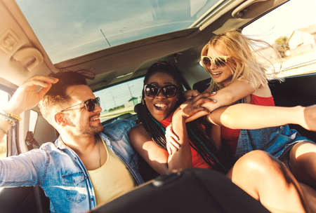 Photo for Three best friends enjoying traveling in the car, sitting in rear seat and having lots of fun on a road trip. - Royalty Free Image