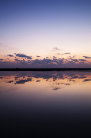 Sunset reflecting clouds in the salt Bacuta, Odiel Natural Park in Huelva (Spain)
