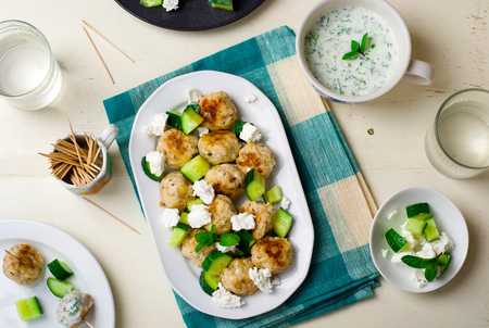 greek chicken meatballs with cucumbers, cheese feta and yogurt sauce. top view, selective focus