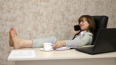 Foto de beautiful business woman sitting in an armchair with bare feet on table resting and drinking tea, coffee. girl at work in office negotiates on mobile phone and works on a computer. - Imagen libre de derechos