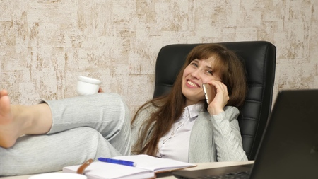 Foto de woman in office drinking coffee resting in workplace. beautiful businesswoman with phone sits in a chair with bare feet on the table resting. girl at work in the office talking on a mobile phone - Imagen libre de derechos