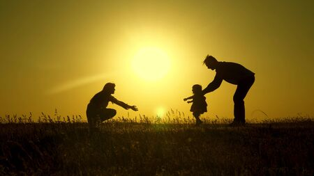 Photo pour parents play with their little daughter. mother and Dad play with their daughter in sun. happy baby goes from dad to mom. young family in the field with a child 1 year. family happiness concept. - image libre de droit