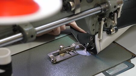 Foto de needle of the sewing machine quickly moves up and down. process of sewing leather goods. Tailor sews black leather in sewing workshop. needle of the sewing machine in motion, close-up. - Imagen libre de derechos