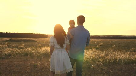 Photo pour Family playing with their daughter in the sunshine. happy child sitting on the hands of parents. Mom and dad play with their little daughter in the park at sunset. family walk with the baby in park. - image libre de droit