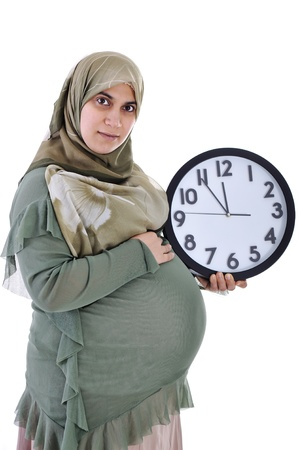 Tummy of pregnant muslim woman with clock