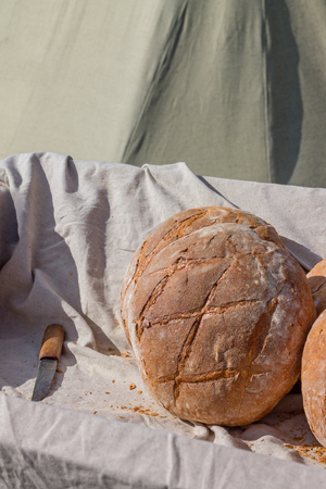 Round hearth bread in the cart on a sunny day outdoors.