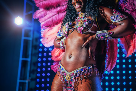 Beautiful bright colorful carnival costume illuminated stage background. Samba dancer hips carnival costume bikini feathers rhinestones close up