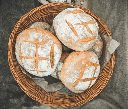 A lot of fresh bread lies in the cart on sunny day outdoors.