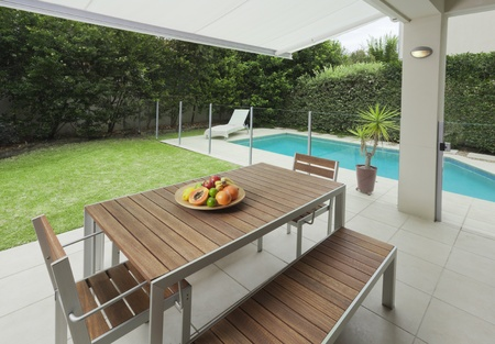 Modern suburban backyard with table setting and swimming pool