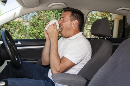 Man allergic to pollen sneezing into hankie inside a car