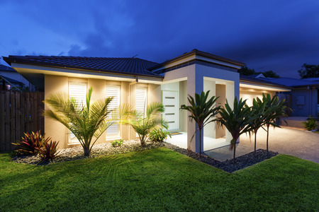 Photo for Well lit modern home exterior at dusk - Royalty Free Image