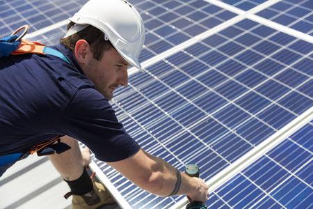 Foto de Solar panel technician with drill installing solar panels on roof on a sunny day - Imagen libre de derechos