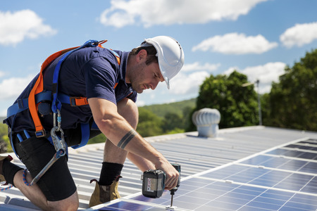 Photo for Solar panel technician with drill installing solar panels on roof on a sunny day - Royalty Free Image