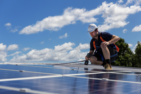 Foto de Solar panel technician with drill installing solar panels on roof on a sunny day - Imagen libre de derechos