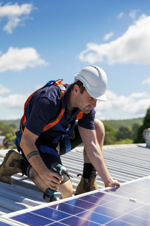 Photo pour Solar panel technician with drill installing solar panels on roof on a sunny day - image libre de droit