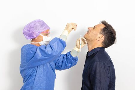 Photo pour A doctor in a protective suit taking a nasal swab from a person to test for possible coronavirus infection - image libre de droit