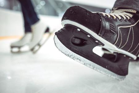 Photo pour Man's hockey skates on ice backgroundMan's hockey skates and women's figure skates on ice background. - image libre de droit
