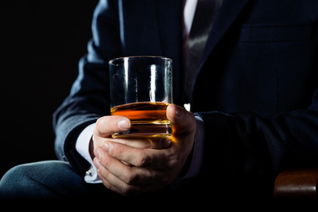 Closeup of serious businessman holding  whiskey to illustrate executive privilege concept