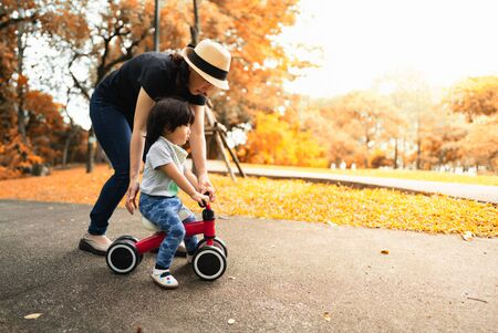 Foto de Cute 2 years old asian toddler learn how to ride a bike helped and protected by her mother in the autumn color season park, concept outdoor family activity time. - Imagen libre de derechos